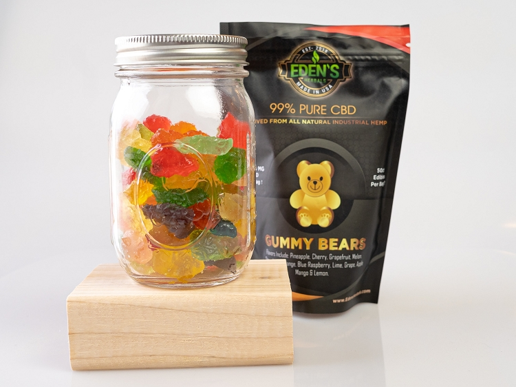 Assorted fruit flavor CBD gummy bears in a mason jar next to an Eden's Herbals bag