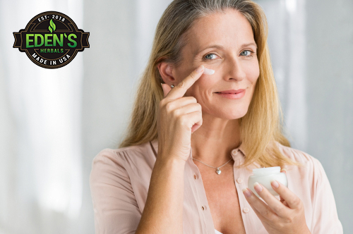 Woman applying Eden's Herbals CBD lotion to her face