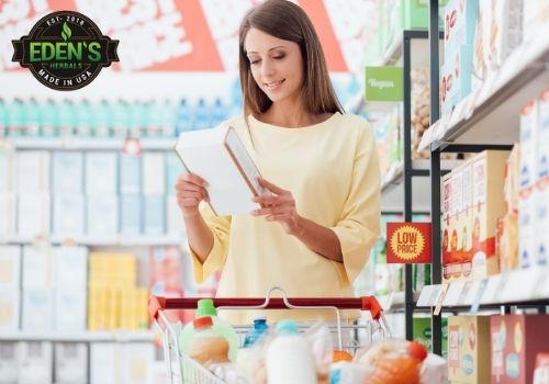 Woman reading nutrition label while shopping for CBD