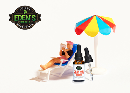 Miniature man in beach chair sun bathing with big bottle of Eden's Herbals CBD Oil next to him