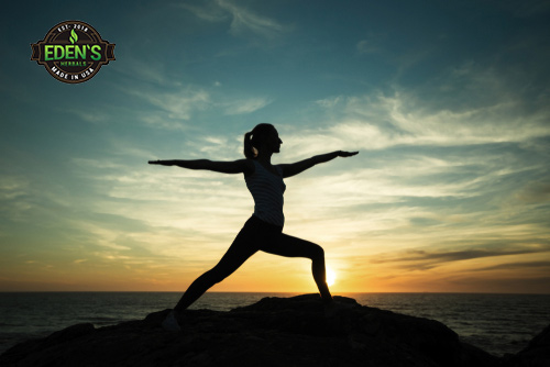 Woman creating healthy lifestyle by doing yoga at sunrise