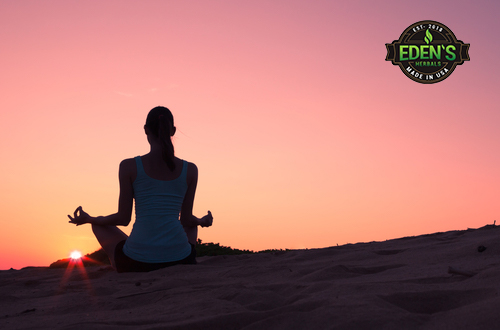 Woman meditating at sunset to relax mind